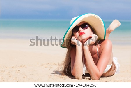 portrait of young beautiful woman on beach with red lips and hibiscus in straw hat - stock photo
