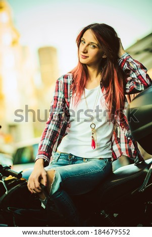 Portrait of young beautiful woman on motorcycle - stock photo