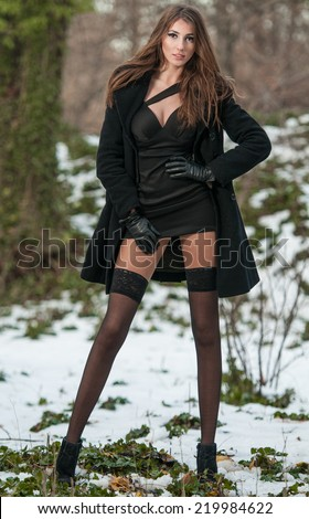 Portrait of young beautiful woman outdoor in winter scenery. Sensual brunette with long legs in black stockings posing fashionable in a park covered with snow. Attractive girl in black in winter shot - stock photo