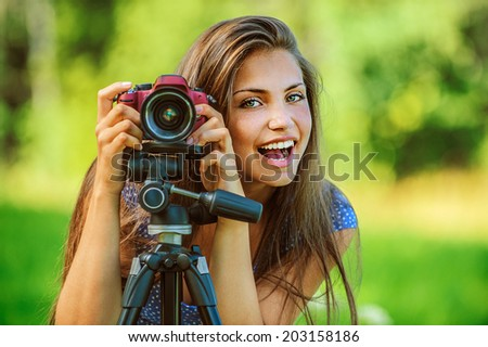 Portrait of young beautiful woman photographed with camera tripod, on green background summer nature. - stock photo