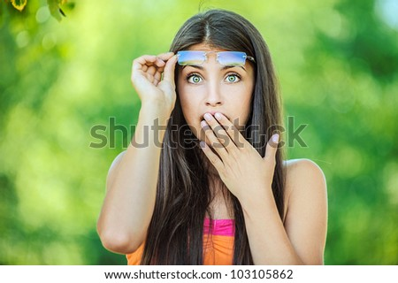 Portrait of young beautiful woman picks up glasses and closes his hand in surprise mouth, on green background summer nature. - stock photo