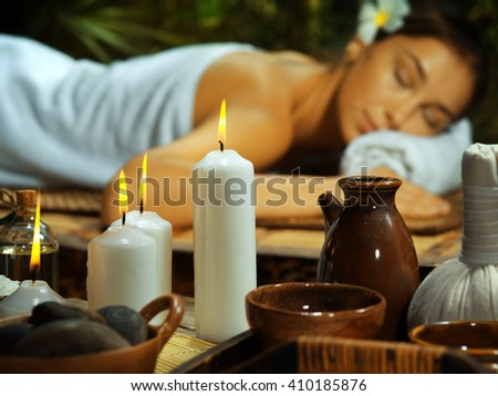 portrait of young beautiful woman  relaxing in spa environment. focused on candle.  - stock photo