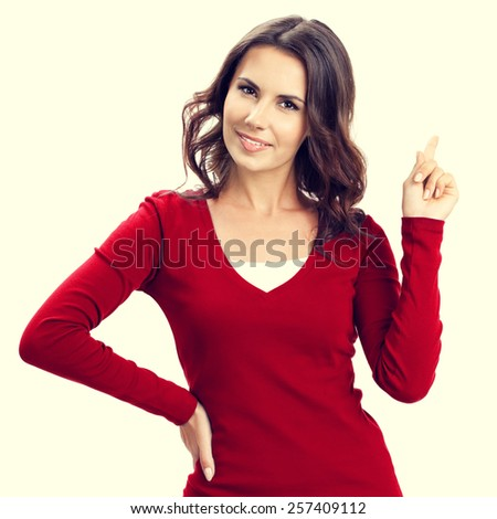 Portrait of young beautiful woman showing copyspace, visual imaginary or something, or pressing virual button - stock photo
