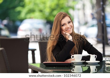 Portrait of young beautiful woman sitting in a cafe outdoor drinking coffee