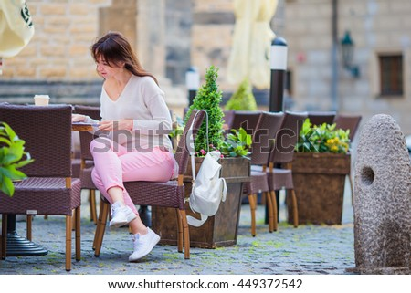 Portrait of young beautiful woman sitting in a cafe outdoor drinking coffee. Happy tourist with newspaper at openair restaraunt - stock photo