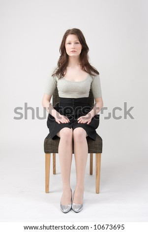 Portrait of young beautiful woman sitting on the chair - stock photo