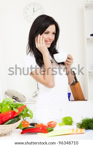 portrait of young beautiful woman talking cell phone, drink coffee or tea in the kitchen, while cooking, prepare vegetable, happy smile - stock photo