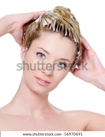 Portrait of young beautiful woman washing her hair - isolated - stock photo