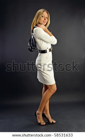 Portrait of young beautiful woman wearing a white dress and holding a handbag on the dark background in the studio - stock photo