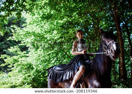 Portrait of young beautiful woman wearing black and white dress riding dark horse at summer green forest.  - stock photo