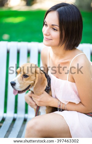 portrait of young beautiful woman with a dog outdoors - stock photo