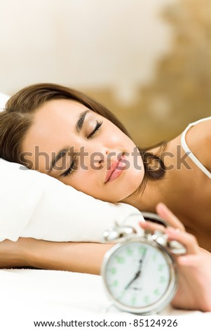 Portrait of young beautiful woman with alarmclock lying on bed, at home