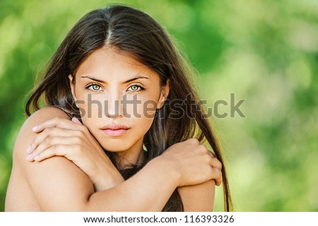Portrait of young beautiful woman with bare shoulders crossed her arms, on green background summer nature.