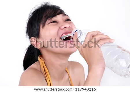Portrait of young beautiful woman with bare shoulders drinks from bottle of cold water, on green background summer nature.