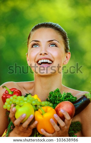 Portrait of young beautiful woman with bare shoulders holding fruit and vegetables - peppers, apples, eggplant, parsley, grapes, on green background summer nature. - stock photo