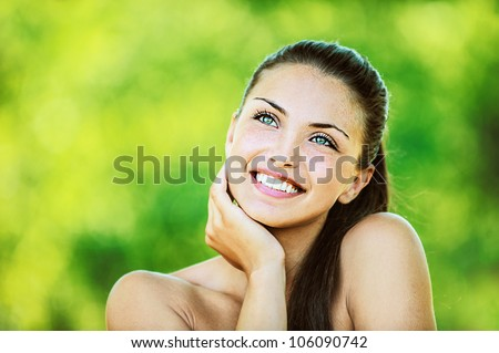 Portrait of young beautiful woman with bare shoulders laughs and looks up and smiling, on green background summer nature. - stock photo