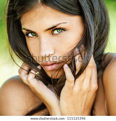 Portrait of young beautiful woman with bare shoulders sad looking at camera, on green background summer nature. - stock photo