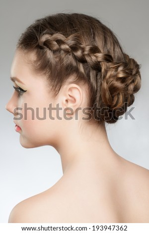 Portrait of young beautiful woman with blond hair and braid hairdo. Rear view, hairstyle with tress - stock photo