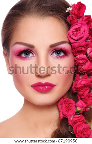 Portrait of young beautiful woman with bright make-up and pink roses in hair - stock photo