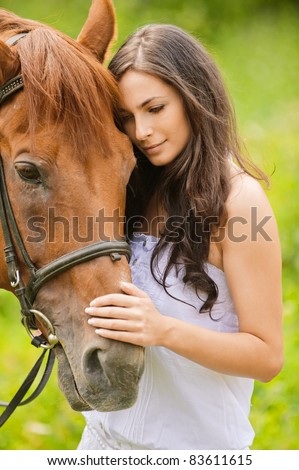 Portrait of young beautiful woman with brown horse at summer green park.