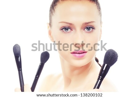 portrait of young beautiful woman with brushes for make-up