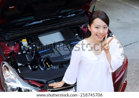 portrait of young beautiful woman with car aside