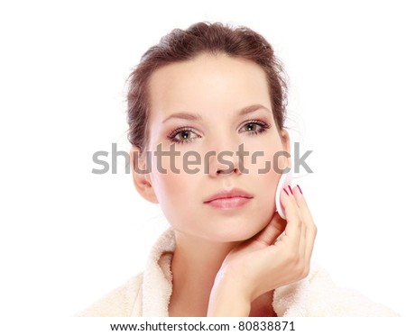 Portrait of young beautiful woman with cotton swab cleaning her face - stock photo
