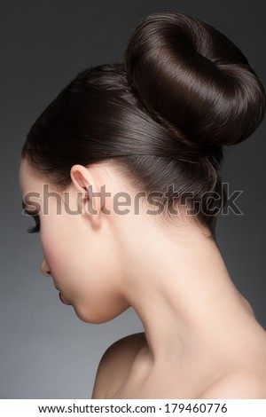 Portrait of young beautiful woman with creative elegant hairstyle, hair bun. Rear view - stock photo