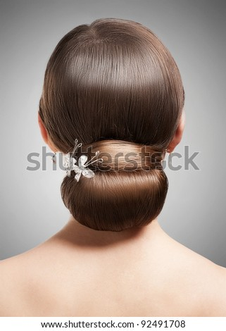 Portrait of young beautiful woman with creative elegant hairstyle, rear view