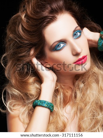Portrait of young beautiful woman with curly shaggy hair style and blue eyes make-up on black background