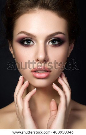 Portrait of young beautiful woman with evening make up touching her face over black background. Multicolored smokey eyes. Luxury skincare and modern fashion makeup concept. Studio shot. - stock photo