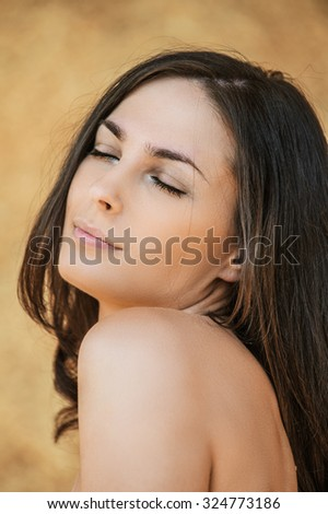 Portrait of young beautiful woman with eyes closed against beige background.