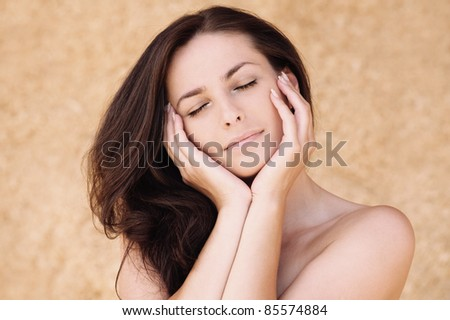 Portrait of young beautiful woman with eyes closed propping up her face against beige background.