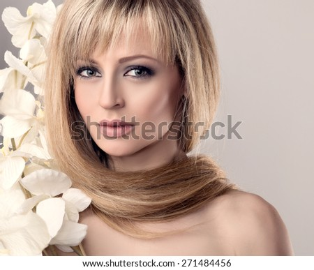 Portrait of young beautiful woman with flowers. Long Hair around Neck. Fashion toned photo.