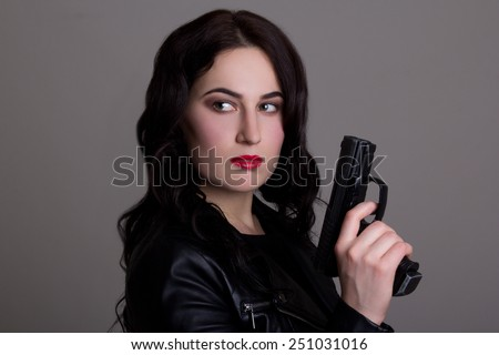 portrait of young beautiful woman with gun over grey background - stock photo