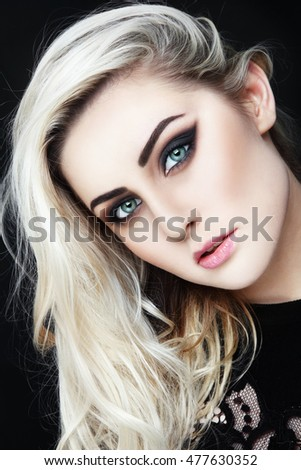 Portrait of young beautiful woman with long platinum blond hair and stylish winged eyes make-up