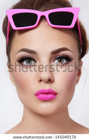 Portrait of young beautiful woman with pink lipstick and stylish vintage sunglasses - stock photo