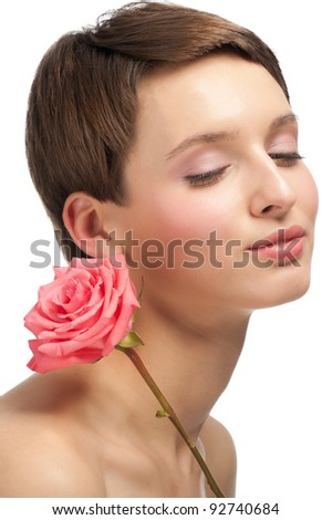 Portrait of young beautiful woman with pink rose and clear make-up