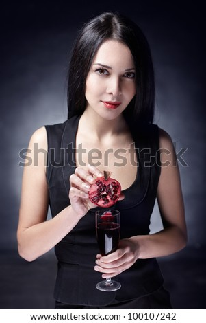 Portrait of young beautiful woman with pomegranates in her hand, on dark background
