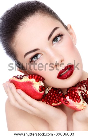 Portrait of young beautiful woman with pomegranates in her hands, on white background - stock photo