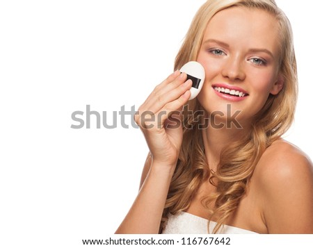 Portrait of young beautiful woman with powder puff. Pretty woman applying makeup. - stock photo