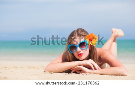 portrait of young beautiful woman with red lips and hibiscus blowing air kiss
