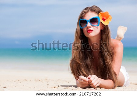 portrait of young beautiful woman with red lips and hibiscus lying at tropical beach - stock photo