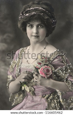 portrait of young beautiful woman with roses flowers. vintage picture from 1911 - stock photo