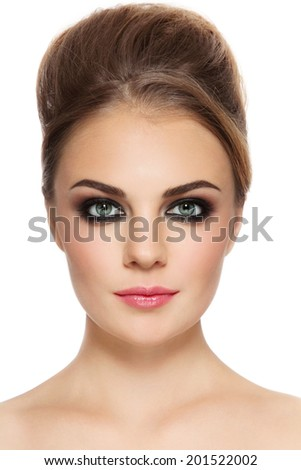 Portrait of young beautiful woman with smoky eyes and hair bun, over white background - stock photo