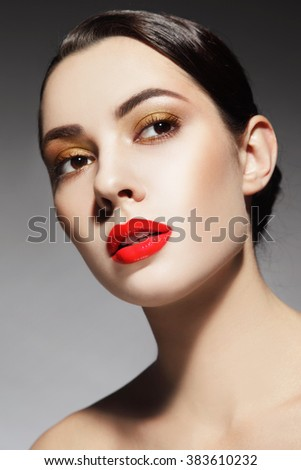 Portrait of young beautiful woman with stylish make-up and glossy red lipstick - stock photo
