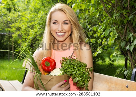Portrait of young beautiful woman with vegetable on green background summer nature. - stock photo