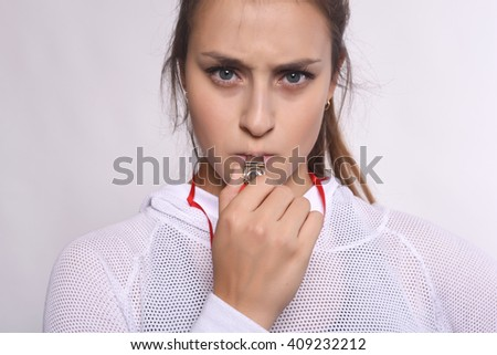 Portrait of young beautiful woman with whistle and serious expression. Isolated white background. - stock photo