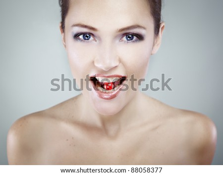 Portrait of young beauty girl with candy in her mouth