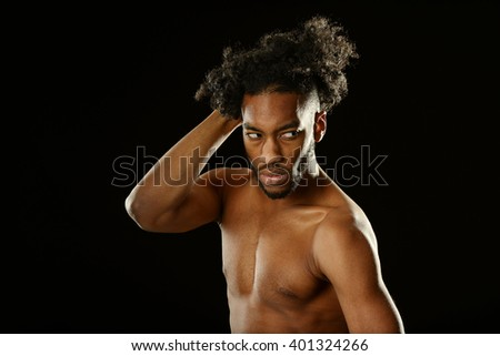 Portrait of young black man with nude torso on a dark background - stock photo